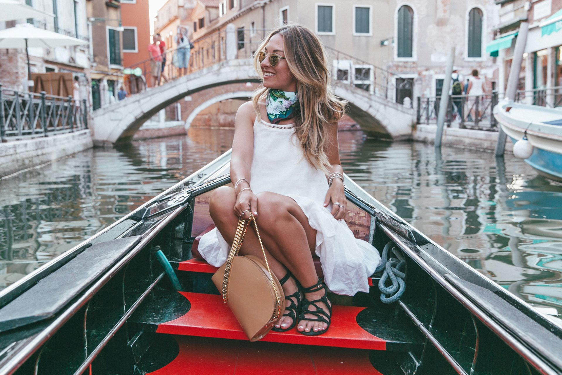Travel blogger Laura McWhinnie from This Island Life cruising through the canals of Venice, Italy in a gondola at sunset.