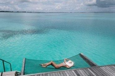 Girl in bikini on net at an overwater villa - Shangri-La's Villingili, Maldives