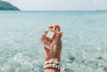 Hand holding Aerin 'Hibiscus Palm' Fragrance against aqua water
