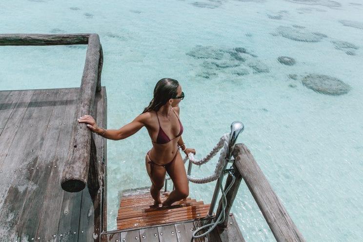 Girl at overwater villa on Bawah Island, Indonesia