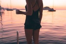 Girl in silk lingerie on sailing yacht at sunrise