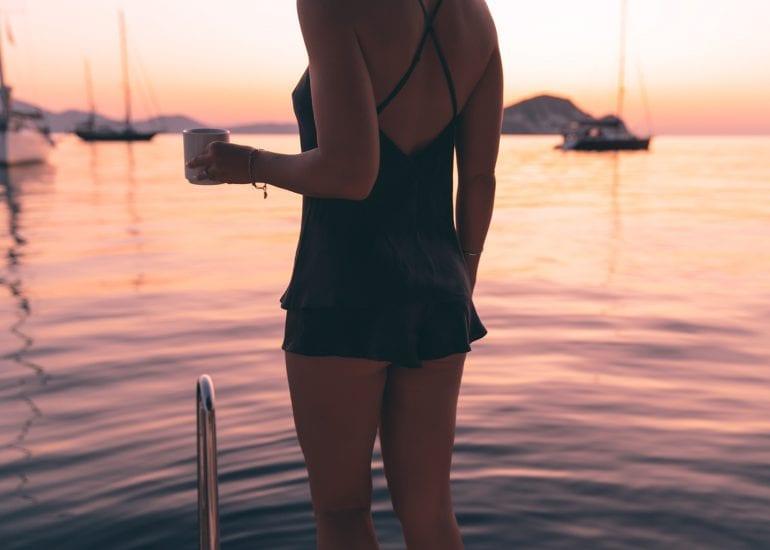 Girl in silk lingerie on sailing yacht at sunrise